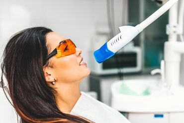 woman getting laser teeth whitening treatment