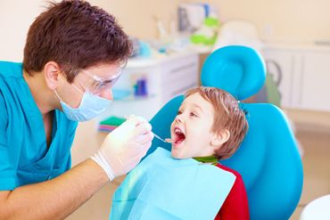 dentist doing oral examination of a kid